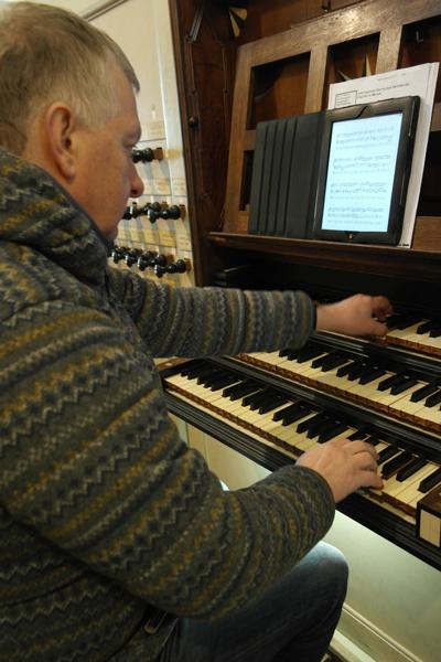 Dick Koomans leest de muziek vanaf zijn iPad . 'Je hebt geen zware tas met muziekboeken nodig. Handig als je op reis bent'