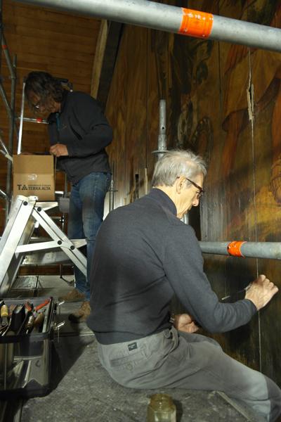 Willem Haakma Wagenaar (voorgrond) en Edwin van den Brink restaureren de schildering boven het orgel